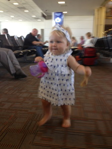 At the airport waiting for our flight. Again our girl all smiles running around the airport.. with pizza of course.